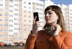 Woman make a call on modern background. Woman orange coat  make a call on modern background Royalty Free Stock Images