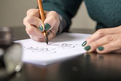 Woman make calligraphy writings, make art on a paper using pen b. Rush and sign pen. Adult, old hands of a calligrapher woman. Lifestyle image of a design stock photos