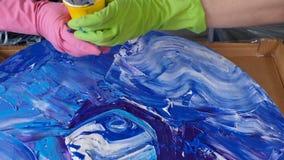 Woman make fluid art acrylic painting. Creative cosmic artwork hippie wallpaper in blue color with hands of creator. Woman make fluid artwork. Fluid art stock footage