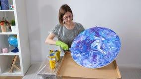 Woman make fluid art acrylic painting. Creative cosmic artwork hippie wallpaper in blue color with hands of creator. Woman make fluid artwork. Fluid art stock video footage