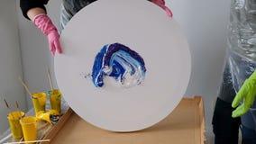 Woman making fluid art acrylic painting. Creative cosmic artwork hippie wallpaper in blue color with hands of creator. Woman make fluid artwork. Fluid art stock video