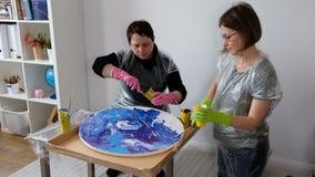 Women make fluid art acrylic painting. Creative cosmic artwork hippie wallpaper in blue color with hands of creator. Woman make fluid artwork. Fluid art stock footage
