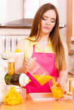 Woman make orange juice in juicer machine pouring drink in glass Royalty Free Stock Photos