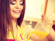 Woman make orange juice in juicer machine pouring drink in glass Royalty Free Stock Images
