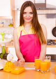 Woman make orange juice in juicer machine pouring drink in glass Royalty Free Stock Photo