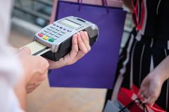 Woman make payment with credit card swipe through terminal. cust. Omer paying with EDC or swiping machine. buy and sell product or service Stock Image
