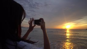 Woman make photo of beautiful sunrise over the ocean on smartphone. Woman make photo of beautiful colorful sunrise over the ocean on smartphone stock video
