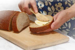 Woman make sandwich. Woman make butter on the bread Royalty Free Stock Photography