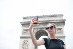 Free Woman Make Selfie With Phone At Arc De Triomphe In Paris, France. Woman With Smartphone At Arch Monument. Vacation And Sightseeing Royalty Free Stock Image - 115036266
