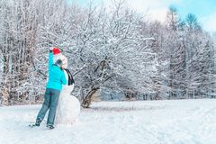 Woman make a snowman in frosty winter day. Concept royalty free stock photo