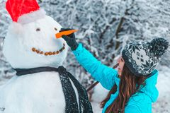 Woman make a snowman in frosty winter day stock photography