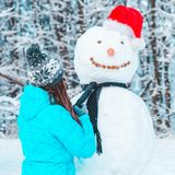 Woman make a snowman in frosty winter day. Concept royalty free stock photography