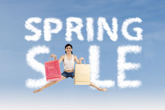 Woman make spring sale sign. Excited woman jumping with cloud design of spring sale sign Stock Photography