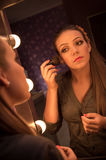 Woman make up. A pretty young woman doing her make up in front of a mirror Royalty Free Stock Photography