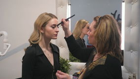 Woman make-up artist doing make-up blonde girl using brushes. Both women in black. Interior decorated in white color. The model is reflected in the mirror. Make stock footage