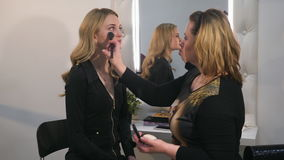 Woman make-up artist doing make-up blonde girl using brushes. The model is reflected in the mirror. Make-up artist applying dry cosmetic tonal foundation on the stock video footage