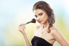 Woman with a make-up brush Stock Images
