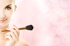 Woman with a make-up brush Stock Photography
