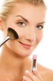 Woman with a make-up brush. Royalty Free Stock Photography