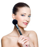 Woman with make-up brushe Royalty Free Stock Image