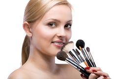 Woman with make up brushes isolated on white Royalty Free Stock Images