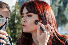 Woman Make up cosmetics / Beautiful young girl make up face powder personally outdoors stock photos