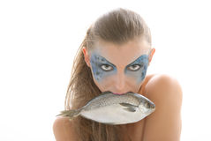 Woman in make-up with fish in mouth Royalty Free Stock Image