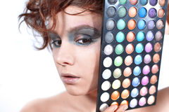 Woman with a make-up holds a cosmetic palette. Royalty Free Stock Image