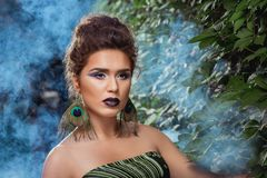 Woman with make up posing against green bush in blue smoke. royalty free stock photography