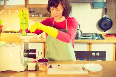 Woman make vegetables juice in juicer machine Stock Images