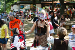 Woman Makes Bubbles Maryland Renaissance Festival. Young woman in medieval costume entertains children by making huge uniquely shaped soap bubbles at the Royalty Free Stock Images