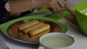 A woman makes a cake from Savoiardi cookies. Dip cookies in syrup and lay on a substrate