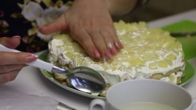 A woman makes a cake from Savoiardi cookies. A woman puts layers of cookies, cream and pineapples. A new layer of pineapples