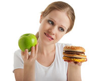 Woman makes choice, healthy and unhealthy foods. Attractive young woman makes a choice between healthy and unhealthy foods, apple and hamburger isolated on white Royalty Free Stock Images