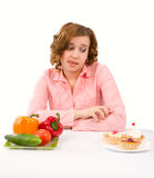 Woman Makes Choice Of Cakes And Vegetables Royalty Free Stock Image