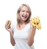 Woman  makes choosing burger and bananas Royalty Free Stock Photo