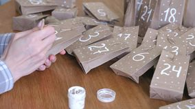 Woman makes christmas advent calendar for kids. Writes a number on the bag by brush and white paint. Close-up hands. Woman makes christmas advent calendar stock video footage