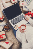 Woman makes christmas shopping online with laptop, above view. Christmas online shopping top view. Female buyer with laptop, copy space on screen. Woman has milk royalty free stock image