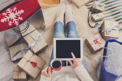 Woman makes christmas shopping online with tablet, above view. Christmas online shopping top view. Female buyer click at screen of tablet, make internet order royalty free stock photos