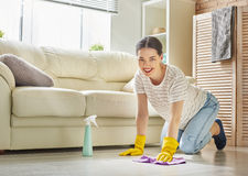 Woman makes cleaning. Beautiful young woman makes cleaning the house. Girl rubs dust Royalty Free Stock Image