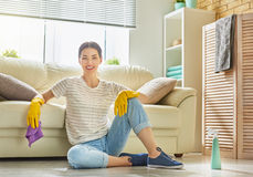 Woman makes cleaning. Beautiful young woman makes cleaning the house. Girl rubs dust Royalty Free Stock Images