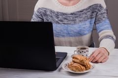 A woman makes a coffeebreak in the workplace. Profiteroles with cream with a Cup of coffee and a laptop. White wooden table royalty free stock image