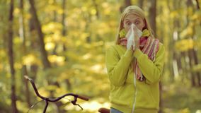Woman makes a cure for the common cold in autumn park. Cold flu season, runny nose. Showing sick woman sneezing at. Autumn park stock video footage