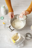 Woman makes the dough in the pan on the white table Stock Photography