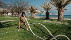 Woman makes exercise with two ropes holding in arms, moving fastly standing on grass outdoors. stock video