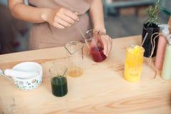 Woman makes handmade cosmetics on wooden table; Stock Photos