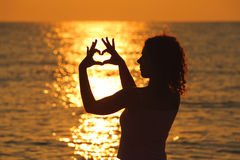 Woman makes heart by hands at sunset Royalty Free Stock Photography