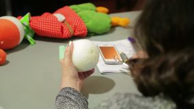 A woman makes a hole in a white foam ball with a scissors for a soft toy