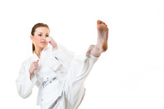 Woman makes a kick. Beautiful caucasian, young, woman makes a kick in karate kimono on white background royalty free stock photo