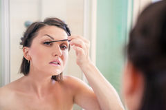 Woman makes light day makeup in bathroom Royalty Free Stock Image